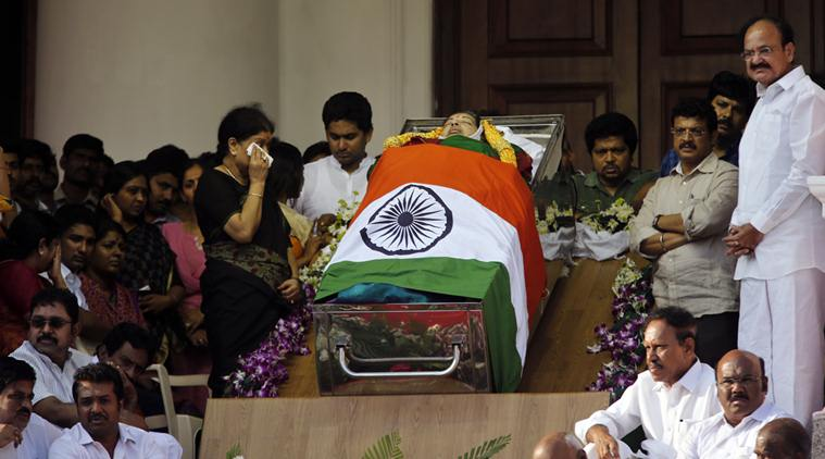 Sasikala Natarajan, left standing, a close friend of India's Tamil Nadu state former Chief Minister Jayaram Jayalalithaa, wipes her tears next to Jayalalithaa's body wrapped in the national flag and kept for public viewing outside an auditorium in Chennai, India, Tuesday, Dec. 6, 2016. Jayalalithaa, the hugely popular south Indian actress who later turned to politics and became the highest elected official in the state of Tamil Nadu, died Monday. She was 68. (AP Photo/Aijaz Rahi)