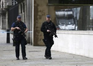 Armed police officers patrol on Whitehall the morning after an attack by a man driving a car and weilding a knife left five people dead and dozens injured, in London