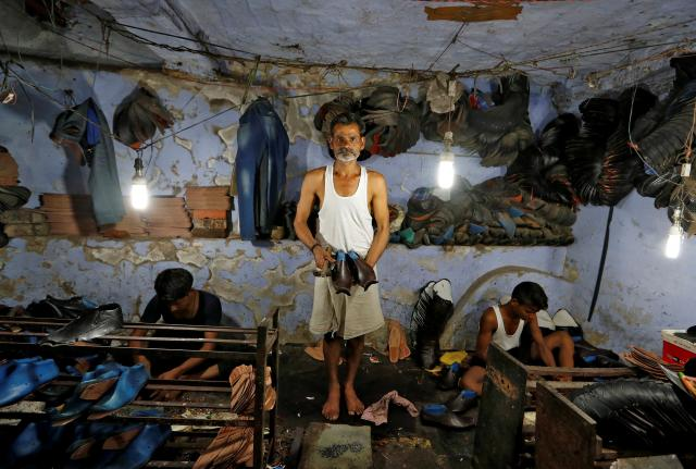 FILE PHOTO: A shoemaker poses for a picture in an underground workshop in Agra, India, June 9, 2017. REUTERS/Cathal McNaughton/File Photo